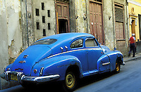Cuba, Havana. Street scene with old antique car