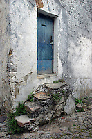 A haunting image of a blue door <br /> suspended above stone steps worn with time.