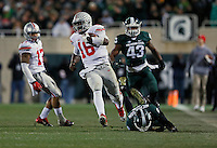 Ohio State Buckeyes quarterback J.T. Barrett (16) breaks tackles by Michigan State Spartans defensive back Montae Nicholson (9) and linebacker Ed Davis (43) on a long run during the fourth quarter of the NCAA football game at Spartan Stadium in East Lansing, Michigan on Nov. 8, 2014. (Adam Cairns / The Columbus Dispatch)
