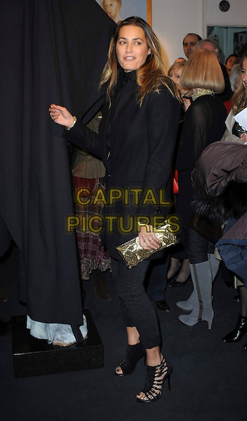 YASMIN LE BON.Model Yasmin Le Bon unveils a statue of herself created by Jonathan Wylder, St. James Gallery, St James, London, England, UK, 24th November 2010..full length  black coat blouse high neck jacket blazer cropped crop trousers clutch bag sandals gold open toe .CAP/WIZ.© Wizard/Capital Pictures.