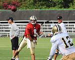 Quarterback Drew Brees delivers a pass to Marques Colston as Head Coach Sean Payton looks on during New Orleans Saints training camp.