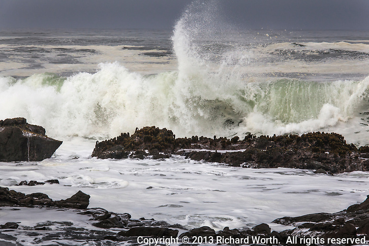 A wave crashes against the rocky shore and sends a plume of ocean water spraying skyward.