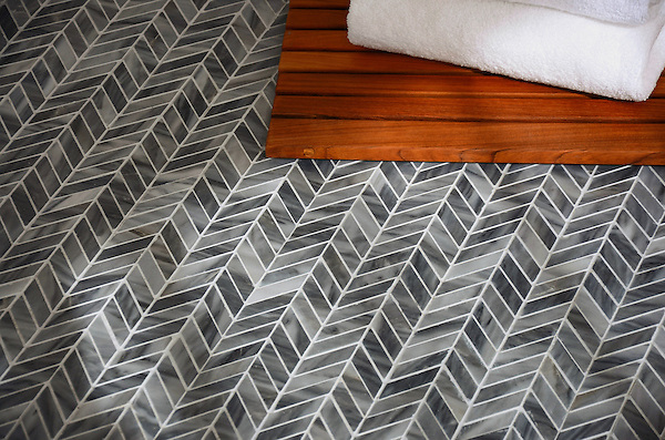 Chevron, a handmade mosaic shown in polished Greystoke, is part of The Studio Line of Ready to Ship mosaics.<br />