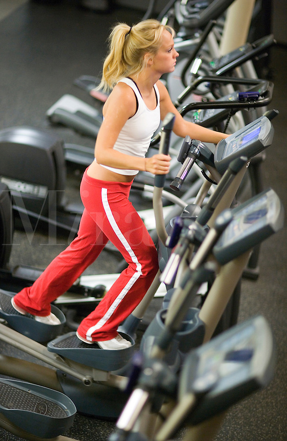 Young woman exercising at her fitness club on aerobic machines.