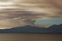 Pictured: Thick smoke is seen billowing over the island of Evia from the beach of Kalamos, across the Evia Gulf, Greece. Wednesday 14 August 2019<br /> Re: Firefighters have been battling a nature reserve wildfire on the island of Evia in central Greece.<br /> Four villages and a monastery have been evacuated.<br /> The country's civil protection authority declared a state of emergency in the area of Evia affected by the fire, where about 280 firefighters, volunteers, soldiers, six water-dropping planes and six helicopters were deployed, along with one more helicopter coordinating the air support.
