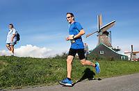 Zaanse Schans -  Deelnemer aan de Zaanse Schansloop loopt langs  Molen de Kat. Toeristen op de dijk kijken toe