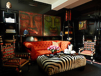 A sofa in the ground-floor study is upholstered in a Romo fabric, the floor lamps are by Nicholas Haslam Ltd. The black-lacquered panelling and the obelisk- shape bookshelves are custom made, the paintings were purchased in Singapore and the sisal rug is by Tim Page Carpets.