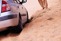 Man standing by car stuck in sand in desert, Tunisia