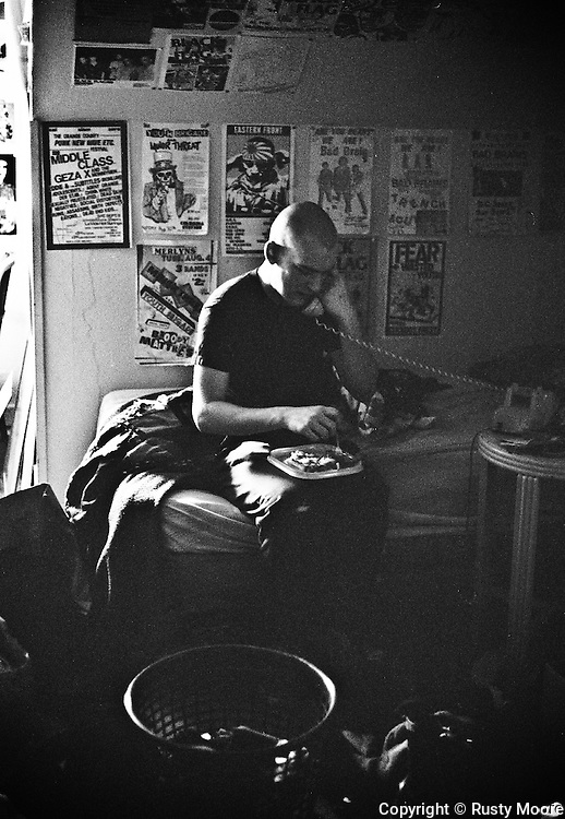 Ian MacKaye of Minor Threat eating lunch in his bedroom at Dischord House, Arlington VA, spring 1982.