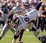 Oakland Raiders vs. Denver Broncos at Oakland Alameda County Coliseum Sunday, October 10, 1999.  Broncos beat Raiders  16-13.  Oakland Raiders linebacker Greg Biekert (54) stops Denver Broncos tight end Byron Chamberlain (86).
