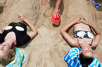 Chloe Lachance-Soulard, 15, (left) of Ottawa, Canada, and cousin Simone Soulard, 14, lay buried under sand sculptures of mermaid tails at Herring Cove Beach in the Cape Cod National Seashore outside of Provincetown, Mass., USA, on Fri., July 1, 2016. Portions of the parking lot have been closed after land eroded during storms earlier this year. This was the girls' first visit to the area.