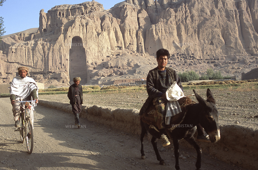 2003..Afghanistan. Bamiyan. Residents pass by the empty place of the Buddha's statue destroyed by the Taliban in March 2001..Afghanistan. Bamiyan. Des habitants passent davant la place vide de la statue de Bouddha, détruite par les Taliban en mars 2001.
