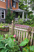 Windowbox container garden on picket fence, birdhouse, house with round porch, tropical looling elephant ear planting, dahlia flowers, lovely landscaping