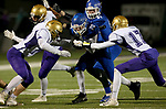 SIOUX FALLS, SD - OCTOBER 25: Parker Nelson #20 from Sioux Falls Christian barrels  through a pair of defenders including Brandon Volmer #17 from Winner in the first half of their 11B playoff game Thursday nigh at Bob Young Field in Sioux Falls.(Photo by Dave Eggen/Inertia)