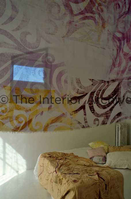 A hand-painted textile hangs over the entrance to the guest bedroom at the far end of the living area