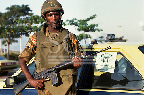 United Nations Conference on Environment and Development, Rio de Janeiro, Brazil, 3rd to 14th June 1992. A Brazilian Marine in uniform with his rifle by a Rio taxi with a Rio 92 poster in the window.