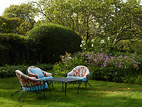Comfortable garden chairs and a table arranged on the lawn in the garden.