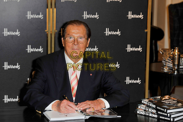Sir Roger Moore.Photocall for the book signing of 'Bond On Bond', Harrods, Knightsbridge, London, England. .11th October 2012.book half length table sitting glasses white shirt pinks stripe tie black blue suit jacket.CAP/MAR.© Martin Harris/Capital Pictures.