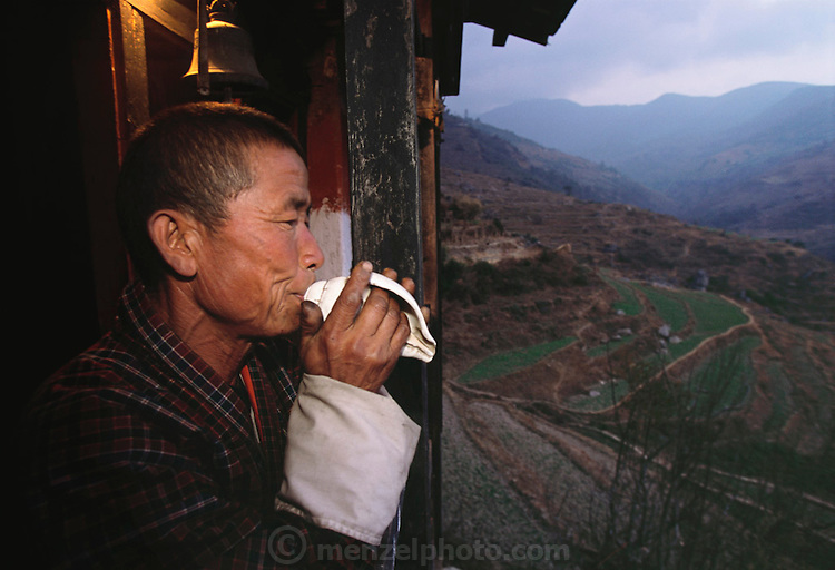 The caretaker of the Shingkhey village Buddhist temple blows a conch shell at the temple window at nightfall, a ritual to ward off evil spirits in the village. From coverage of revisit to Material World Project family in Bhutan, 2001.