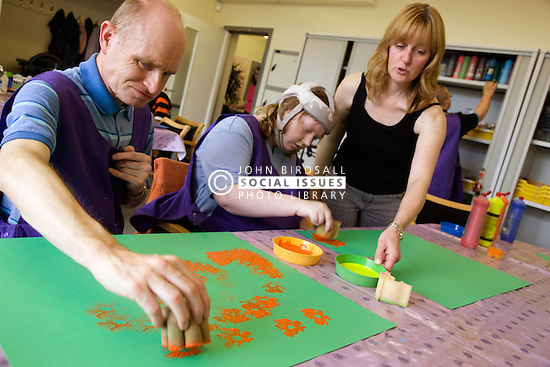 Day Service Officer chatting to service users with learning disability during a painting session,