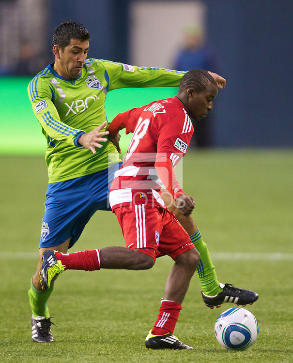 Seattle Sounders FC defender Leonardo Gonzalez , left, tries to steal the ball from Dallas FC forward Marvin Chavez during play between the Seattle Sounders FC and Dallas FC at Qwest Field in Seattle Saturday May 14, 2011. Dallas won the game 1-0.