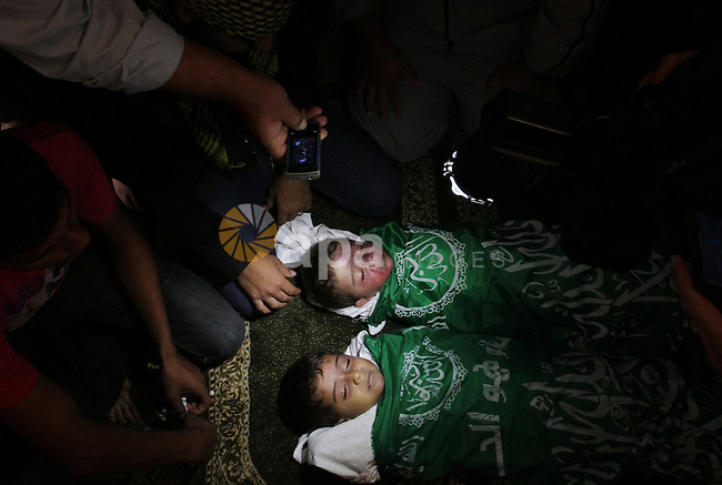 Relatives of Foud Hijazi, 45, grieves over the bodies of her son and grandsons Suhaib, 2, and Mohammed, 4, killed in an Israeli strike, during their funeral at a mosque in the Jebaliya refugee camp, in Gaza Strip, Tuesday, Nov. 20, 2012. Efforts to end a week-old convulsion of Israeli-Palestinian violence drew in the world's top diplomats on Tuesday, with President Barack Obama dispatching his secretary of state to the region on an emergency mission and the U.N. chief appealing from Cairo for an immediate cease-fire. Photo by Sameh Rohmi