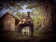 An elderly african-american man sits on a chair in his friend's backyard and plays his acoustic guitar.