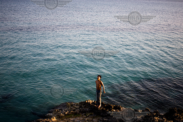 A boy stands on a rock on the coast by the Mediterranean Sea.