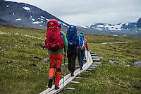 Hikers walk on wooden planks between Alesjaure and Tjäktja, Kungsleden trail, Lapland, Sweden