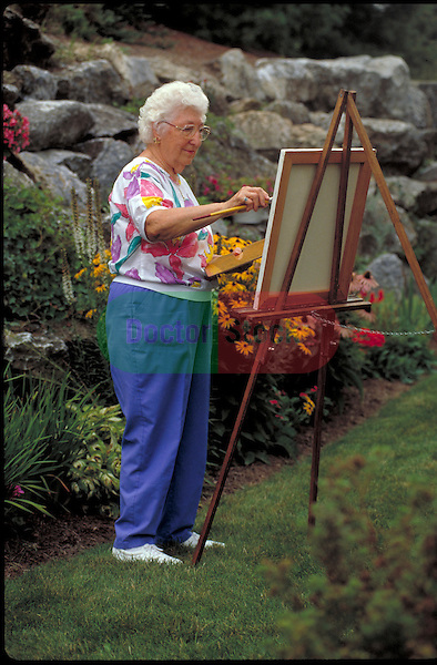 elder woman painting in garden