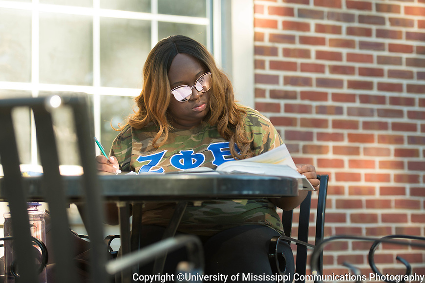 Randesha Moore takes advantage of a cool morning to study on the front stoop of the library.  Photo by Kevin Bain/University Communications Photography.