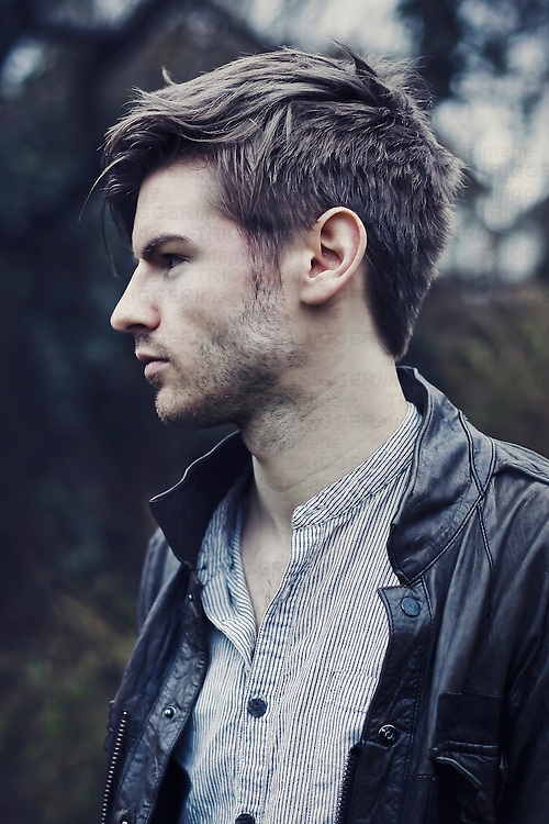 Profile portrait of a young man wearing a striped shirt and a leather jacket, looking away, with blurry garden background.