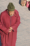 A man with a burgandy robe and green hat on a street in Marrakesh, Morocco.
