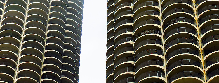 The Marina City Towers seen on the Chicago Architecture Foundation's river cruise. Marina City is a mixed-use residential/commercial building complex that occupies an entire city block on State Street in Chicago, Illinois. It sits on the north bank of the Chicago River in downtown Chicago, directly across from the Loop district. The complex consists of two corncob-shaped, 587-foot (179 m), 65-story towers, which include five-story elevators and physical plant penthouses. It also includes a saddle-shaped auditorium building, and a mid-rise hotel building, all contained on a raised platform next to the Chicago River. (DePaul University/Jamie Moncrief)