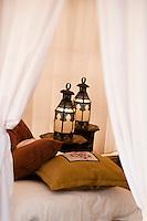 Detail of lanterns and soft furnishings inside a tent at the Ubari Magic Lodge