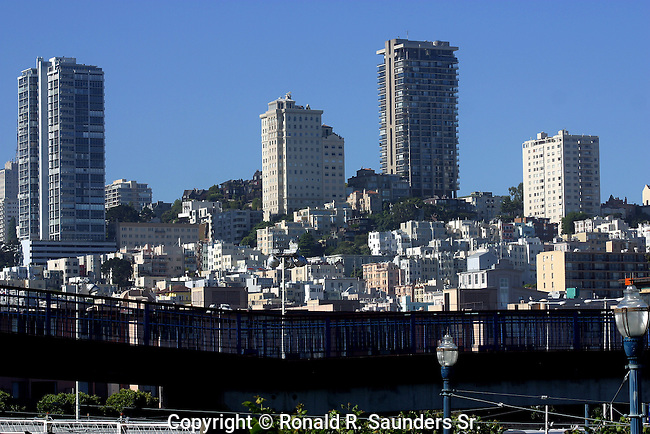 SAN FRANCISCO HI-RISE APARTMENT BUILDINGS on HILLSIDE and LOWER LEVEL BUILDINGS BELOW. WALKING BRIDGE in FOREGROUND