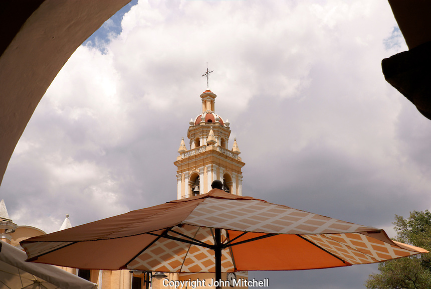 Steeple of Parroquia San Pedro and restaurant umbrella, Cholula, Puebla, Mexico. Cholula is a UNESCO World Heritage Site.