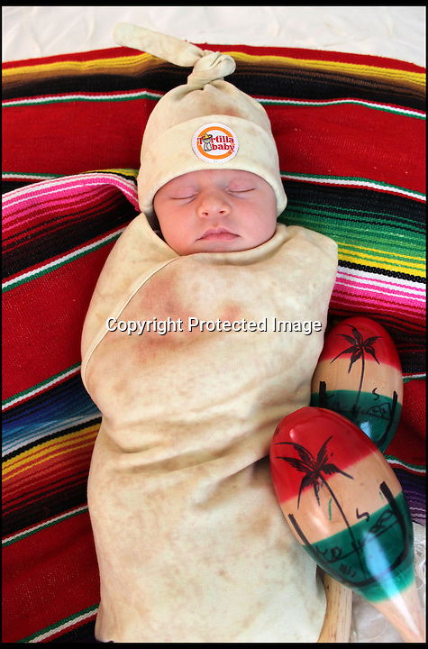 BNPS.co.uk (01202 558833)<br /> Pic: BNPS<br /> <br /> Toddler-tilla!  Mothers can now make their newborn baby look just like a freshly wrapped Mexican burrito by wrapping them in a brand new tortilla blanket.<br /> <br /> The 40 inch circular swaddle blanket is made from a mixture of cotton and polyester and comes with a hat, for babies aged between 0 and 3 months.  Its design is based on an actual photograph of a flour tortilla.<br /> <br /> The hat can easily be placed on the baby's head, which can be adjusted by pulling the knot on the top.  Katharine Owens, from San Jose, California, founded Bon Vivant Baby and designed the tortilla blanket.