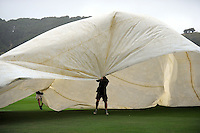 Ground staff try to secure the covers on Day One of the first test between the New Zealand Black Caps and Bangladesh at Hawkins Basin Reserve in Wellington, New Zealand on Thursday, 12 January 2017. Photo: Dave Lintott / lintottphoto.co.nz