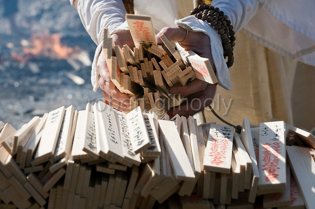 "A priest from the Shingo sect  of Buddhism collects wooden prayer tablets known as ""nadegi"" to throw on the flames of a fire used in a purification ritual at Mt. Takao near Tokyo, Japan on March 14 2010."
