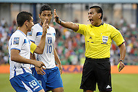 Referee Walter Lopez issues a yellow card and has words with Johnny Leveron (16) and Alexander Lopez (10) Honduras... Mexico defeated Honduras 2-1 after extra time to win the CONCACAF Olympic qualifying trophy at LIVESTRONG Sporting Park, Kansas City, Kansas.