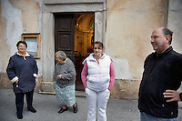 Switzerland. Canton Ticino. Corippo. Pia Scettrini (left), Gabriela Scettrini (center left), Anita Gaggetta (center right) and Marco Castelli (catholic priest) talk together outside the church after the evening mass. Corippo lies in the Verzasca valley. With a population of just 16, Corippo is the smallest municipality in Switzerland. Despite this, it possesses the trappings of communities many times its size such as its own coat of arms, a town council consisting of three local citizens (Pia Scettrini as vice mayor) and a village church. A town council is a democratically elected form of government for small municipalities. A council may serve as both the representative and executive branch. The village has maintained its status as an independent entity since its incorporation in 1822. 8.05.13 © 2013 Didier Ruef