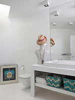 Turquoise woven baskets provide storage in an open fronted washstand in the bathroom