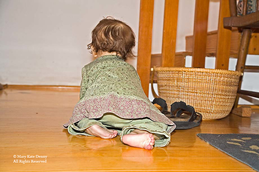 Female baby one year old crawls to stairway on indoor floor