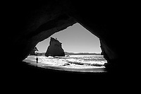 person walking into sea-cave at Cathedral Cove, Coromandel, New Zealand.