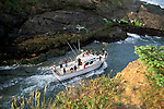 Fishing boat heading to sea between narrow rock channel, world's smallest natural navigable harbor, Depoe Bay, Oregon Coast