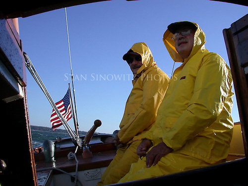 Mary Loring is sailing with a balance rig as seen by the neutral tiller.  The two sailors are dressed for spray in rough seas.