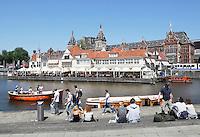 Nederland Amsterdam . Toeristen wachten op een rondvaartboot bij Centraal Station. Op de achtergrond restaurant Loetje. Foto Berlinda van Dam / Hollande Hoogte