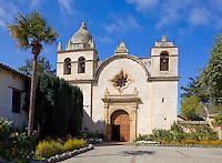 Monterey County, CA<br /> Towers and facade of the Carmel Mission Basilica (1797) above the courtyard gardens - Mission San Carlos Borromeo del Rio Carmelo