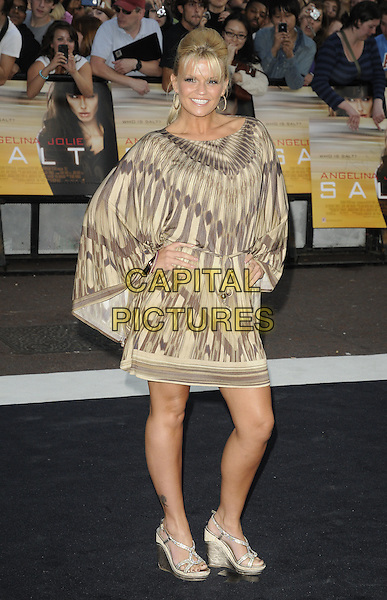"""KERRY KATONA .Attending the UK Film Premiere of """"Salt"""", Empire cinema, Leicester Square, London, England, UK, .August 16th 2010..full length brown beige cream prink dress hands on hips sleeves kaftan poncho wedges gold tanned .CAP/CAN.©Can Nguyen/Capital Pictures."""